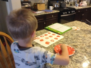 "Kona says the short vowel sound before stamping a ""pumpkin"" on the letter."