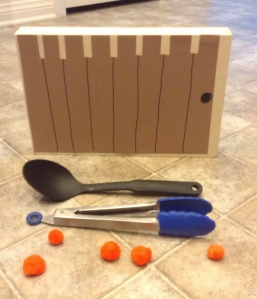 The objective of this activity is to use kitchen utensils, not fingers, to get the orange pom poms (representing the pumpkins) on top of the box (the gate from the story.)
