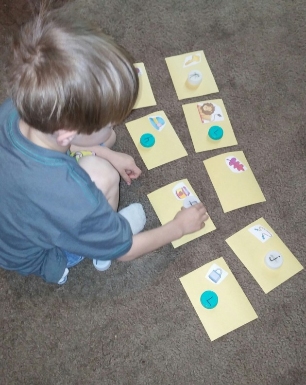 Kona matches the letter of the beginning sound with the picture cards.