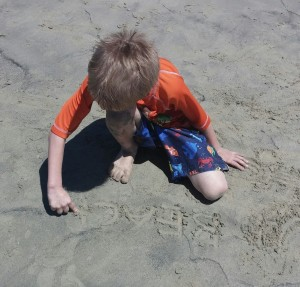 Kona practiced some spelling words in the sand.