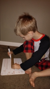Kona practiced drawing lines to the nearest inch using a wooden ruler.
