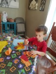 First Tahoe tore pieces of orange, yellow, and red tissue paper to represent the fire. He brushed on a solution of glue and water to get the tissue paper to stick to the blue background.