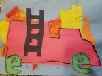 """I had Tahoe outline the construction paper fire engine and lowercase e cut-outs (representing the wheels), with a black sharpie pen. Then he glued them and the ladder cut-out over the (dried) tissue paper """"fire."""""""