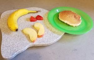 I provided Kona with a pancake, banana, apple slices, and a cut strawberry.