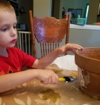 After placing his drawings on the pot, he sealed the pictures by brushing on some more Mod Podge.